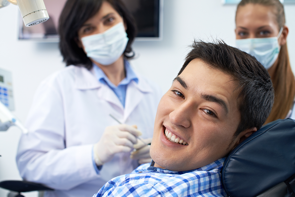 man-dental-patient-in-dental-chair-smiling-with-white-teeth-and-straight-smile-after-oral-care-with-smiling-dentist-and-assistant-in-background-at-dentist