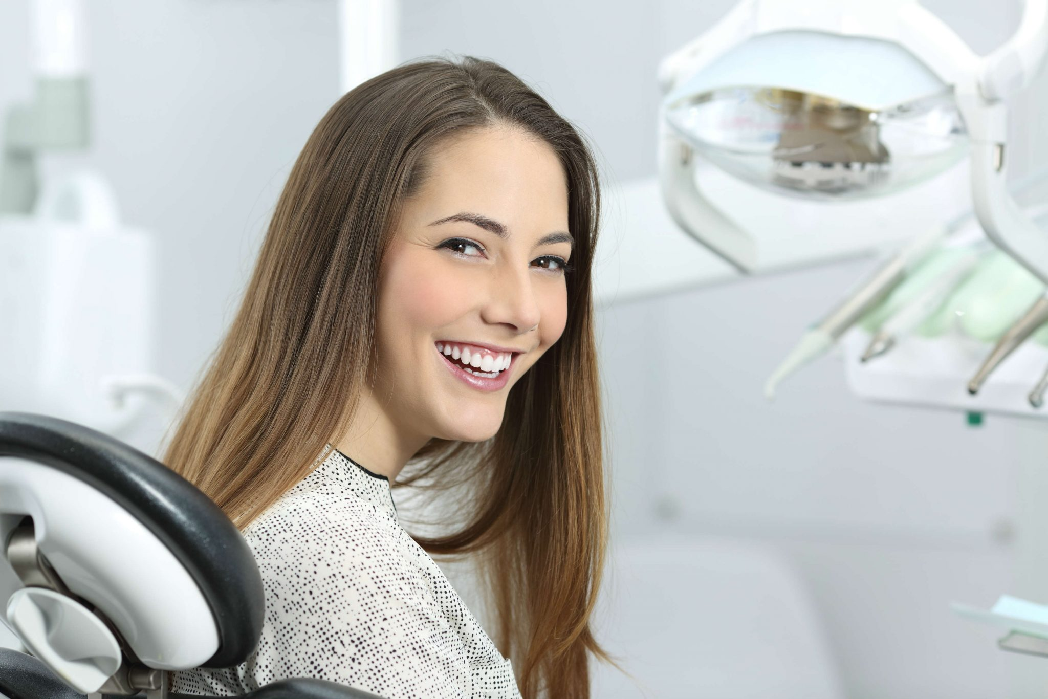 woman-sitting-in-dentist-chair-smiling