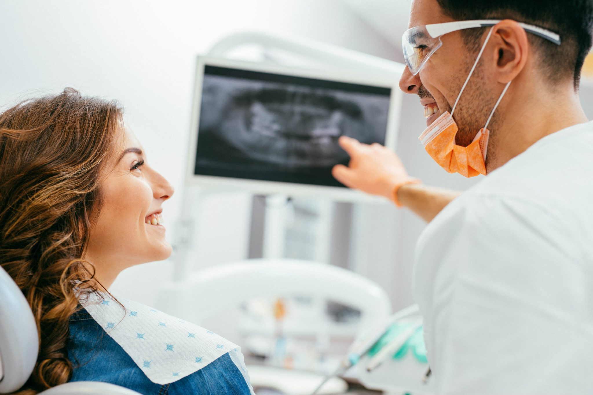 male-dentist-in-dentist-office-presenting-xray-picture-on-monitor-to-female-smiling-dental-patient
