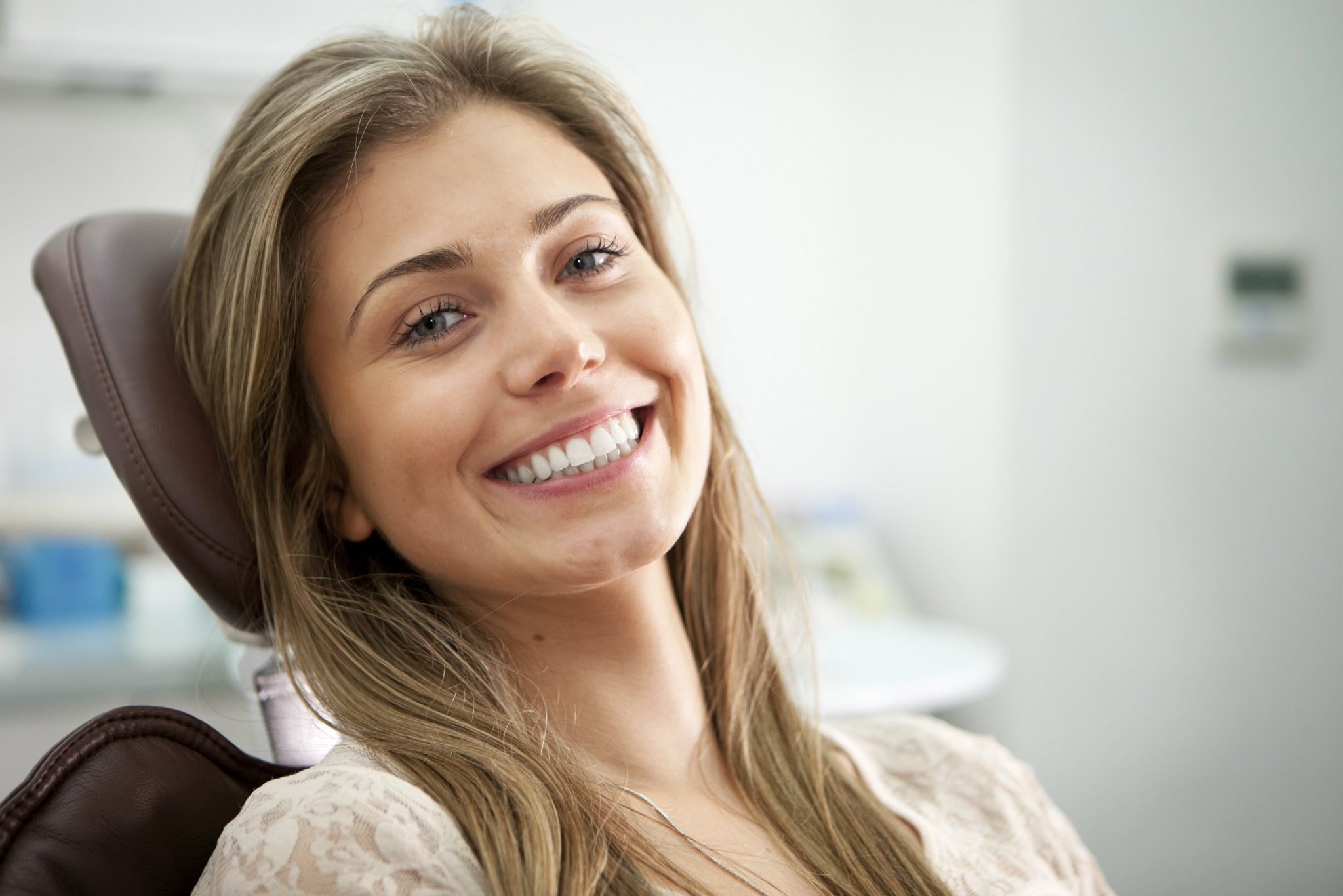 woman-smiling-while-sitting-with-head-laid-back-on-dentist-chair