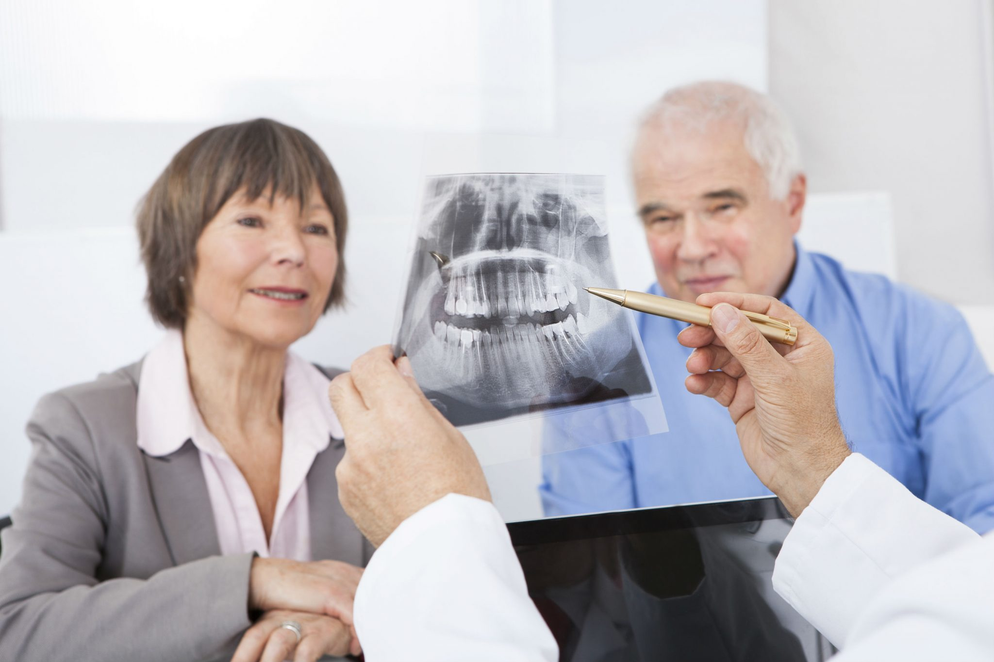 dentist showing xray to senior couple for cosmetic procedure